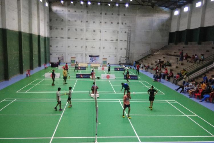 A few people can be seen playing badminton at an indoor stadium A few can be seen seated in the gallery area