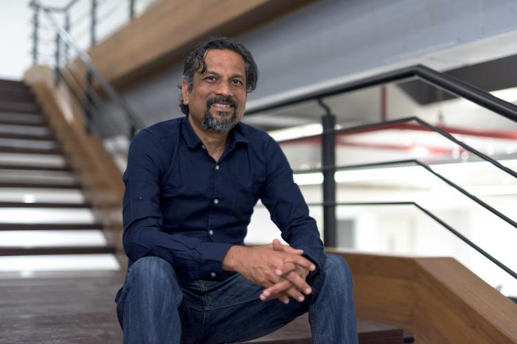 Sridhar Vembu wearing a dark shirt and jeans, sitting on a staircase looking at camera and smiling to his right