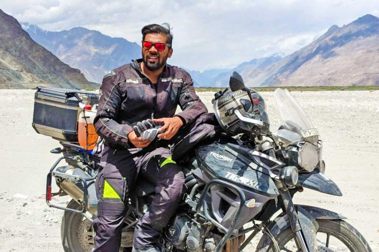 Sriman Kotaru dressed in full biking gear standing leaning onto his Tiger bike