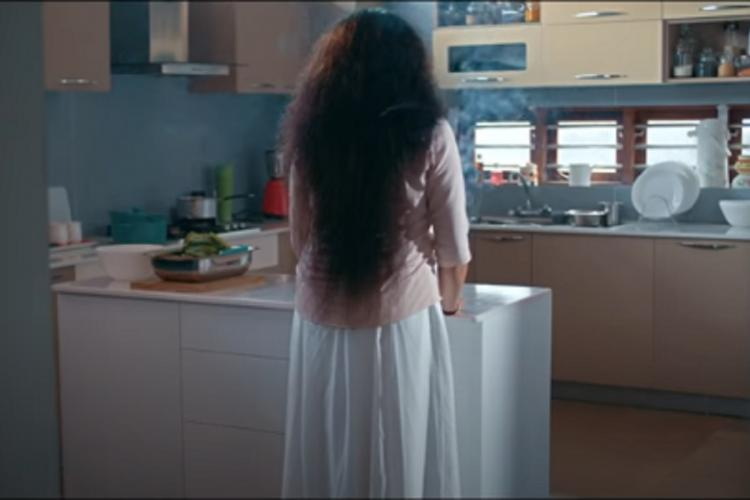 The back of a woman standing in a kitchen with her long thick hair let loose