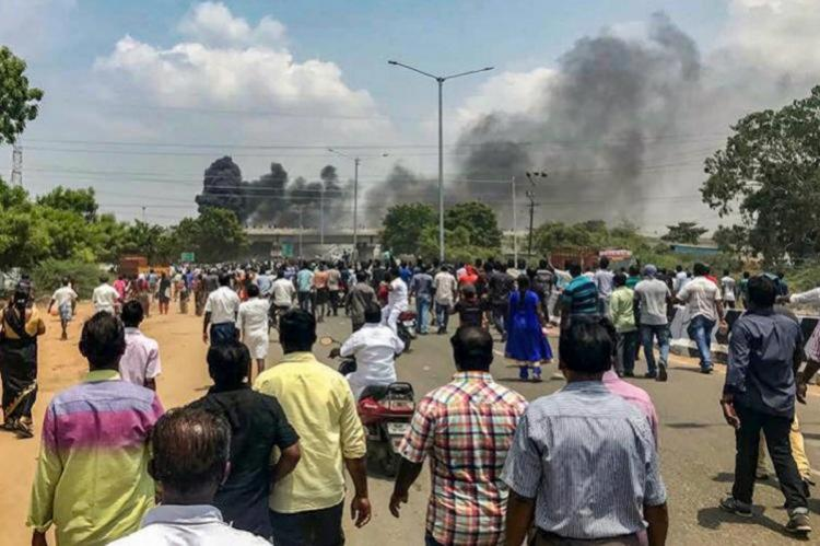 Anti-sterlite protesters watch as smoke engulfs the air in the distance during the 2018 protests