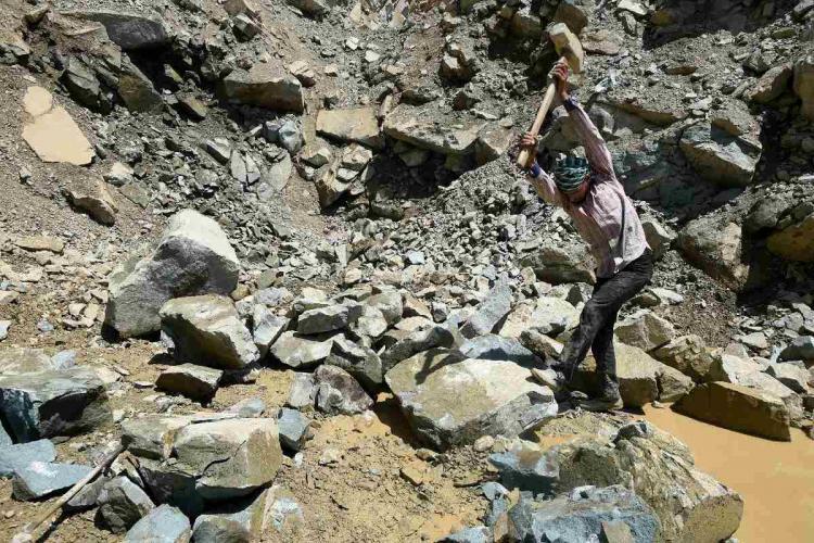 A labourer working at a stone quarry at Athwajan near Srinagar