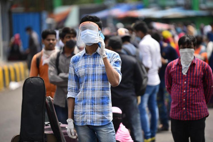 Migrants and Stranded passengers wait outside Secunderabad Railway Station to board trains as Indian Railways resume transport services a man wearing a mask and a white and blue checks shirt is seen talking on the mobile
