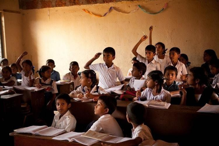 Representative image of students in a classroom where many of them are raising their hands