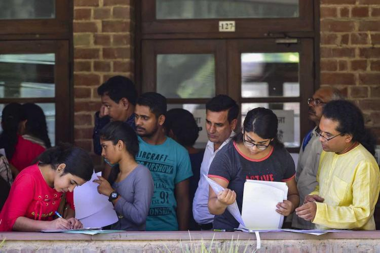 Students fill their admission forms for the new academic session at Hindu College in New Delhi Monday July 1 2019