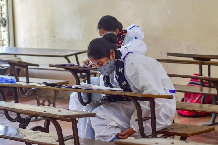 Two students sitting at individual wooden desks in an examination hall wearing PPE and masks
