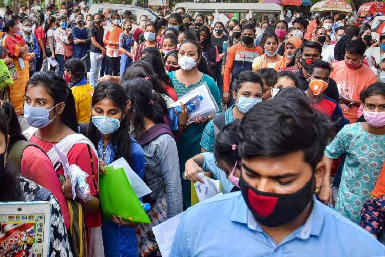 Many students crowded wearing masks and holding books and files at Cotton University in Assam
