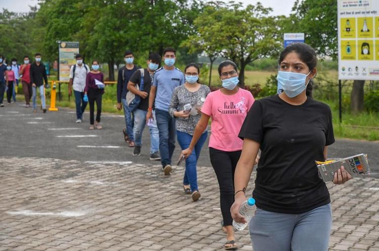 Students wearing face marks stand in a line while maintaining physical distance as they appear for JEE Main exam