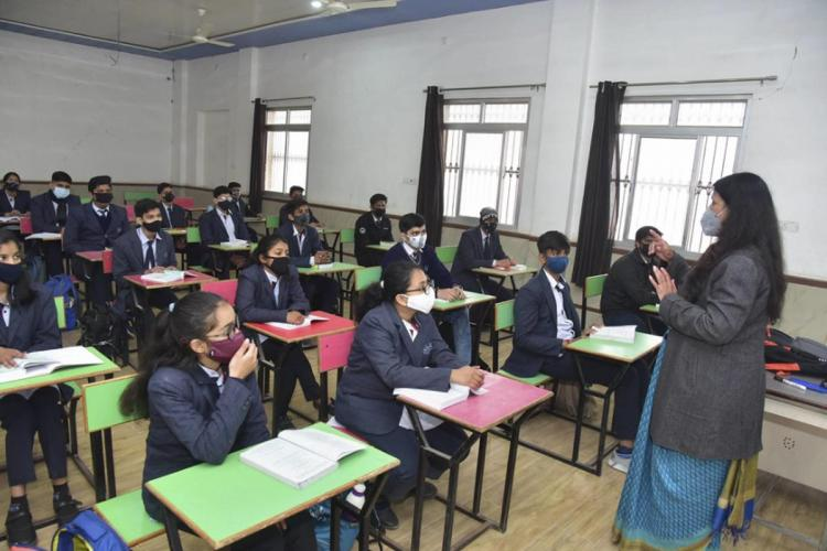 Students are seen sitting in a classroom wearing masks and staggerd seating The teacher is also wearing a mask