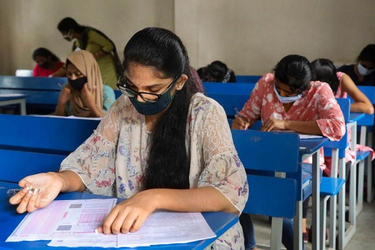 Students writing entrance exam wearing masks