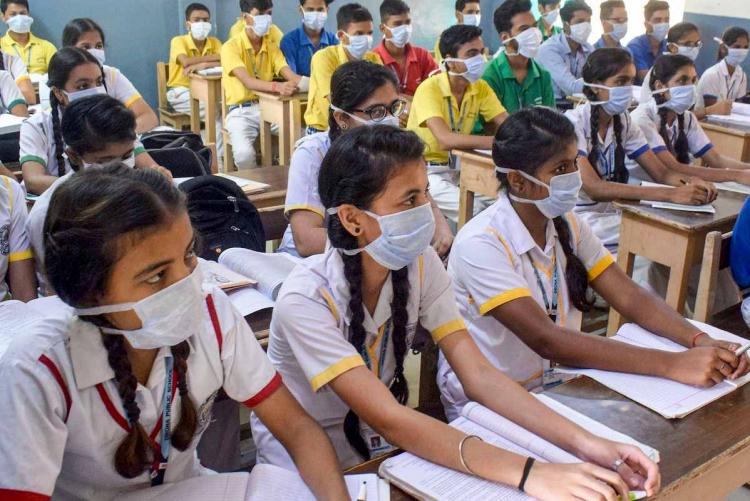School students sitting in classroom with masks on their face