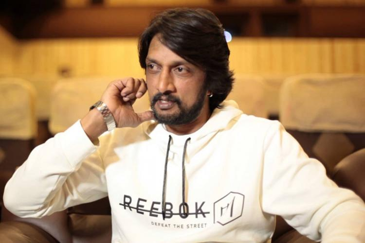 Actor Sudeep is seated looking to his right his right hand touching his jaw He is wearing a white long-sleeved t-shirt and seems to be in the middle of a conversation