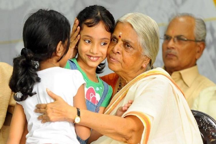 Sugathakumari hugs two little girls sitting on a chair