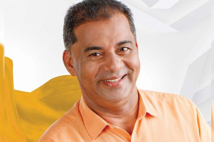 LDF-back independent candidate Sulaiman Haji is wearing an orange shirt and smiling in this image.