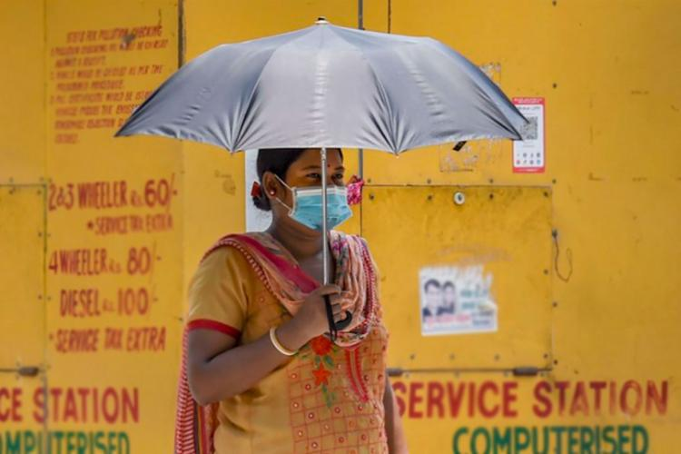 Woman wearing face mask holds a black umbrella and stands in front of a yellow wall