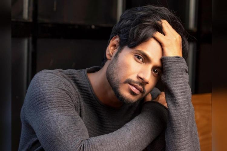 Sundeep Kishan is seen wearing a full sleeved gray tee in the image while striking a pose.