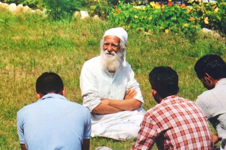 Sunderlal Bahuguna wearing a white kurta and a white turban sitting in the grass with three men sitting in front of him