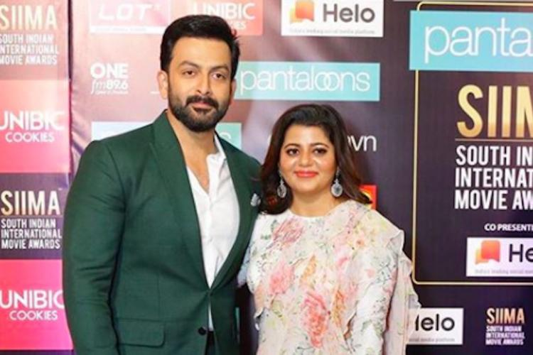 Prithviraj in a dark suit and white shirt posing with his wife Supriya Menon who is dressed in a white outfit