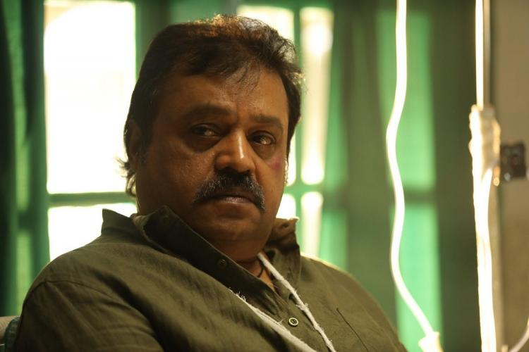 Suresh Gopi in a pale green shirt and a white tag around his neck look away sitting in what seems to be a hospital room