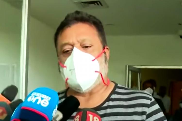 A screenshot of Suresh Gopi speaking to the media at a hospital in Kerala He is wearing a t-shirt and a mask