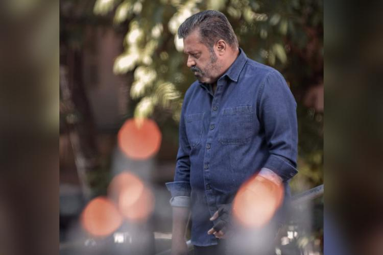 Suresh Gopi wearing a blue shirt looks sideways and down standing among a few trees