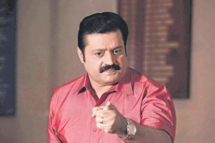 Suresh Gopi in a red shirt pointing finger at the camera