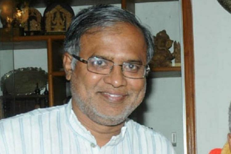 Primary and Secondary Education Minister B Suresh Kumar in a white striped shirt smiling at the camera