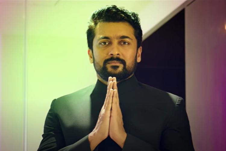 Suriya in black suit showing namaste
