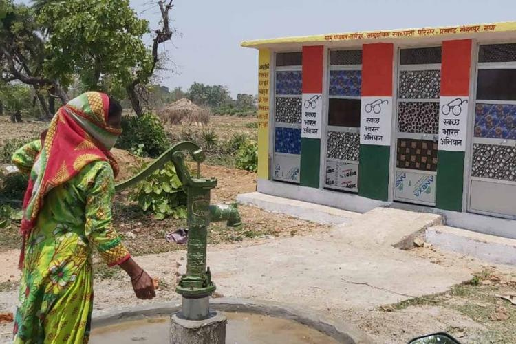 A woman in a green salwar kameez with a red shawl wrapped around her head pumps water from a hand pump her back to the camera A few toilets built under the Swachh Bharat Mission can be seen in the background