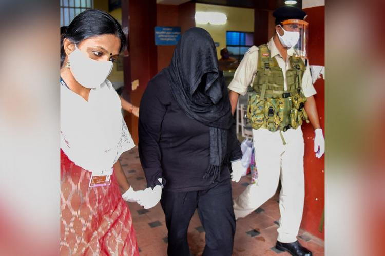 Swapna Suresh accused in Kerala gold smuggling case coming out of court in a black dress that with her face covered
