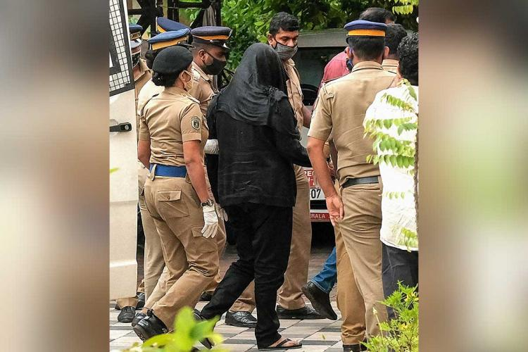 Gold smuggling accused Swapna Suresh along with police officialsSwapna clad in a black pants and top has also covered her face