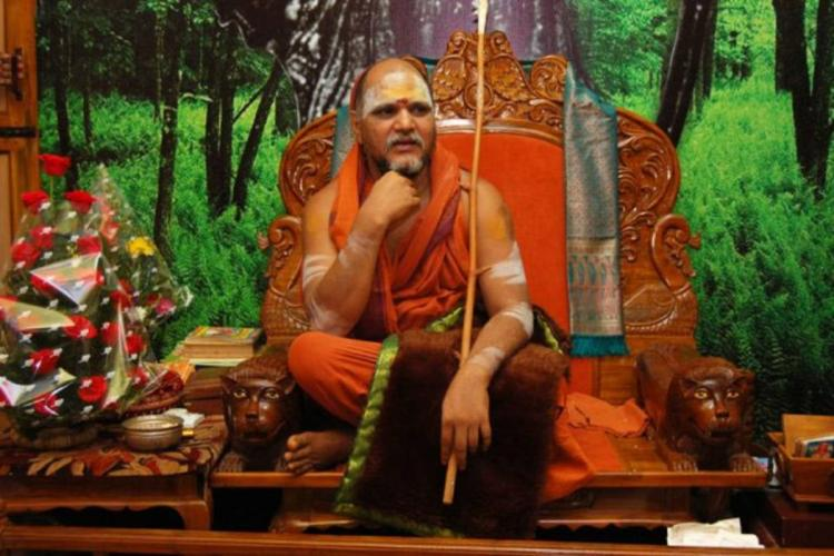 Swaroopanandendra Saraswathi in orange robes seated in an orange chair holding a stick