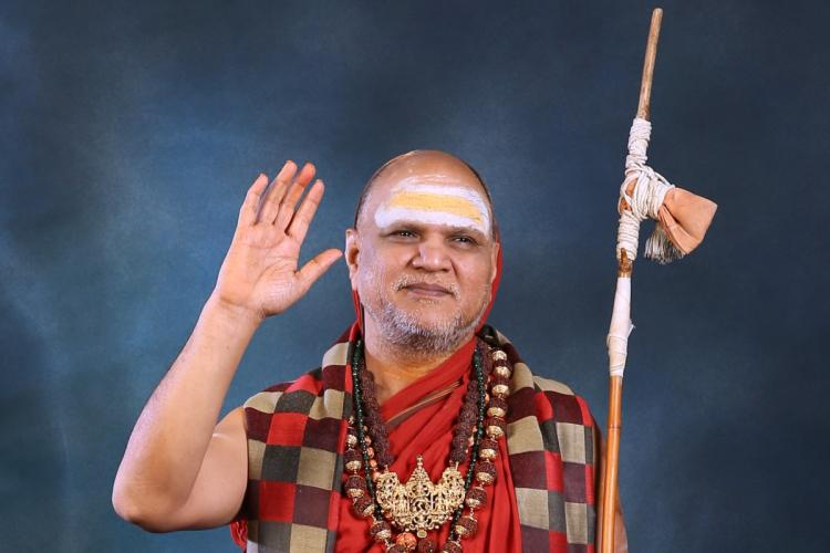 Swami Swaroopanandendra Sawarathi wearing orange robes holding a stick and holding his right hand up