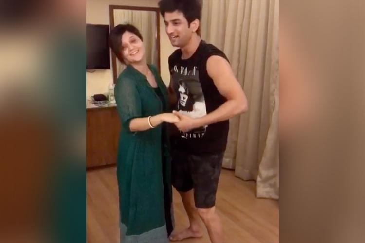 Screengrab from video shared by Swastika Mukherjee where she and Sushant Singh Rajput are dancing. She is wearing a long flowy green outfit while Sushant is wearing black shorts and t-shirt. Both are smiling.