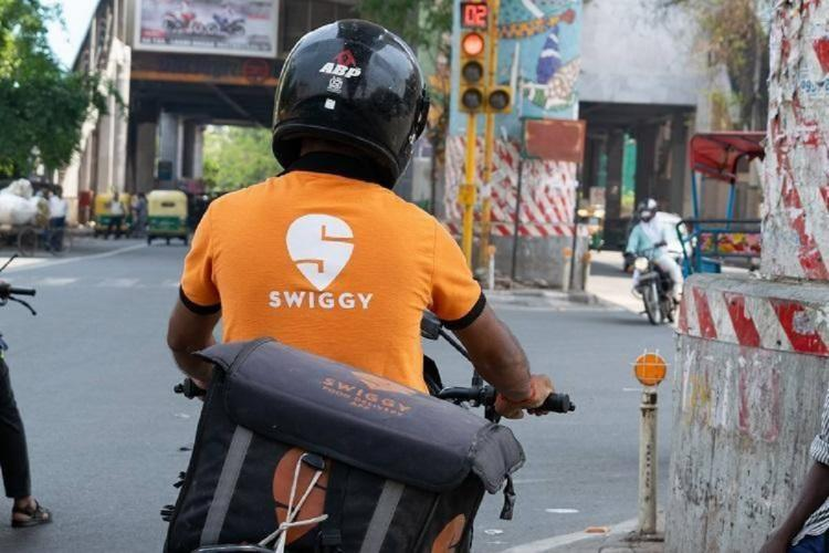 A swiggy delivery executive sitting on a bike wearing the companys orange tshirt with logo emblazoned on it