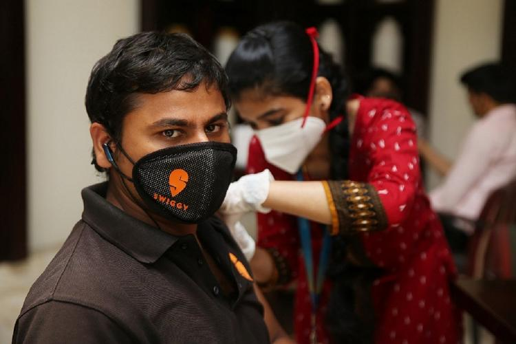 A Swiggy delivery executive being administered the vaccine man looking at camera with a swiggy logo on his mask