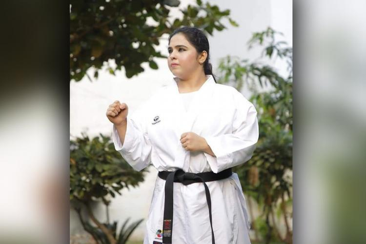 Syeda Falak in her Karate uniform and a black belt