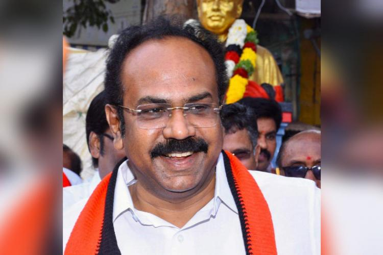 Thangam Thennarasu in a white shirt with an orange and black cloth draped around his neck