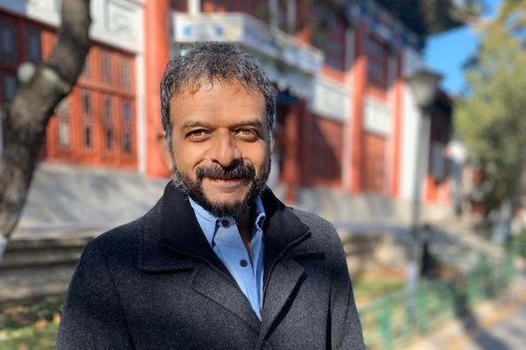 Musician TM Krishna wearing a grey blazer and smiling into camera