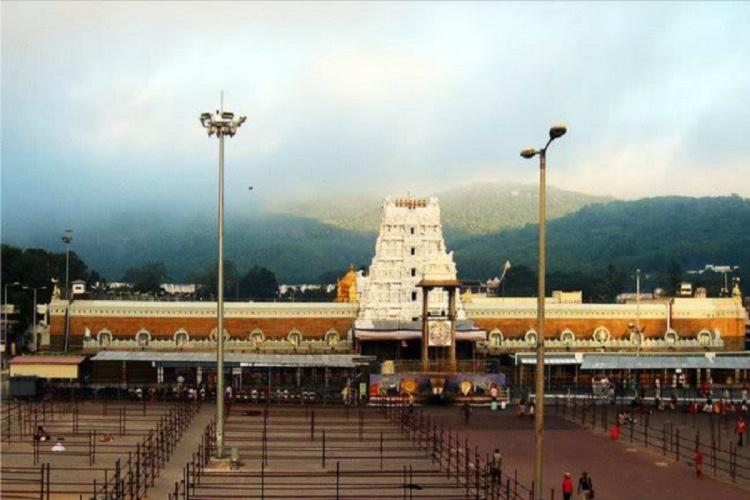 Wide image of the Tirupati Tirumala temple with hills and foggy sky in the background