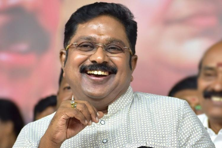 Dhinakaran laughs he is wearing an off white shirt has one hand in front of his chin and others are behind him laughing