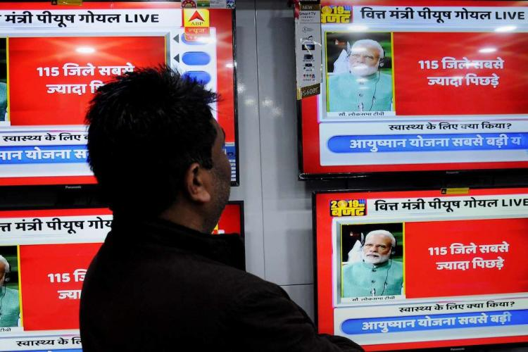 A man watches the interim Union Budget 2019-20 being presented on television screens at a shop in Amritsar Friday Feb 1 2019
