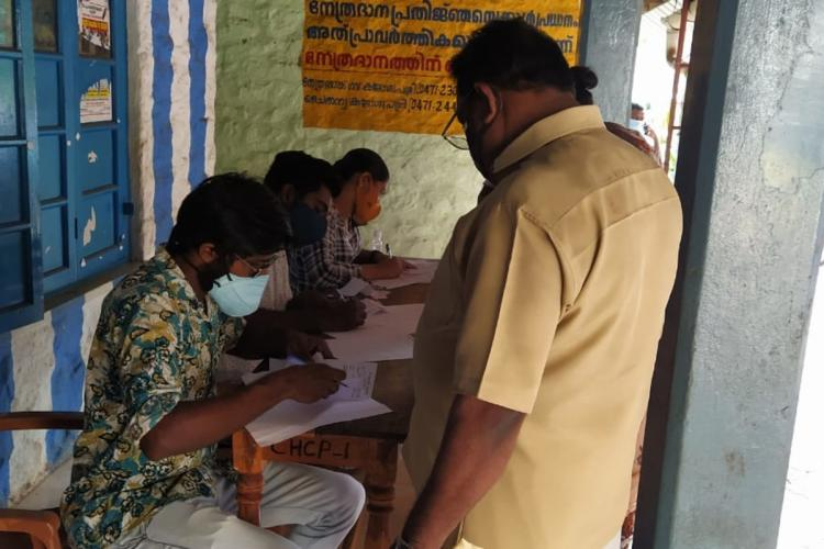 A group of three men from the NGO Coastal Students Cultural Forum sitting at a table, helping a man with vaccine registration in Kerala