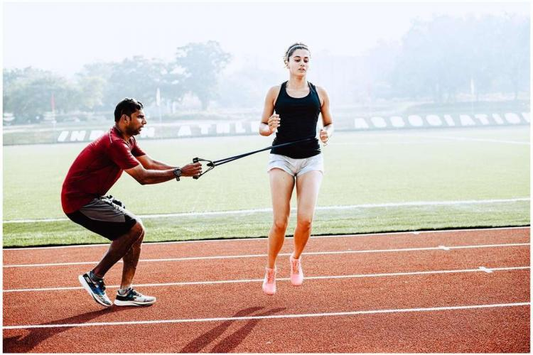 Taapsee jumps on a running race ground as an instructor guides her