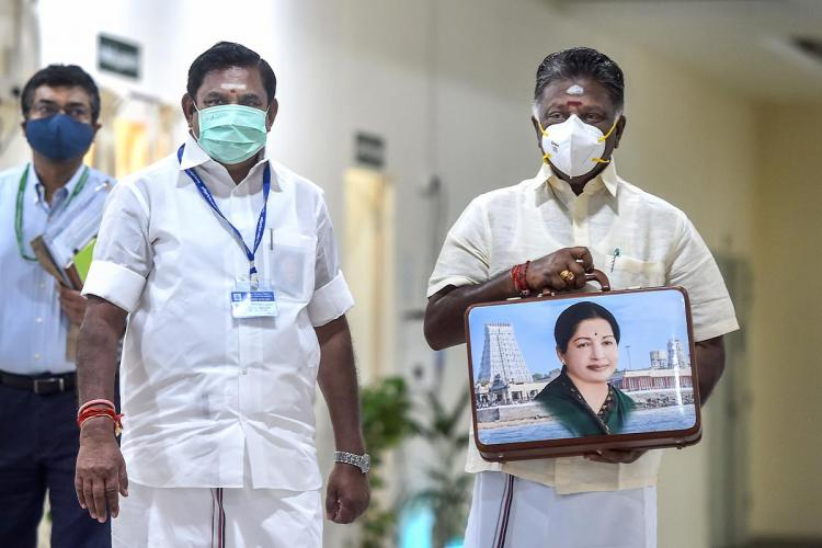 Chief Minister Edappadi Palanisamy and Deputy CM O Panneerselvam holding a suitcase with J Jayalalithaas image imprinted on it before presenting the Tamil Nadu Interim Budget 2021-22