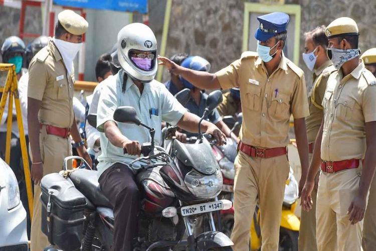 Police officers inspecting a bike rider