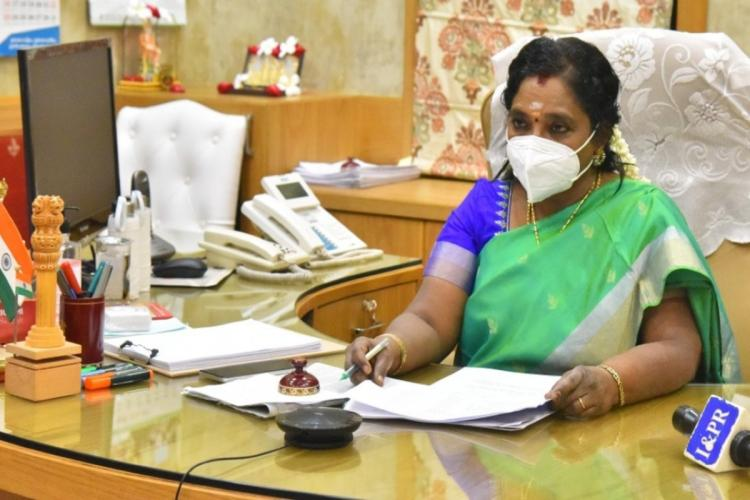 Telangana Governor Tamilisai Soundararajan sitting at her office desk wearing a mask in a green saree