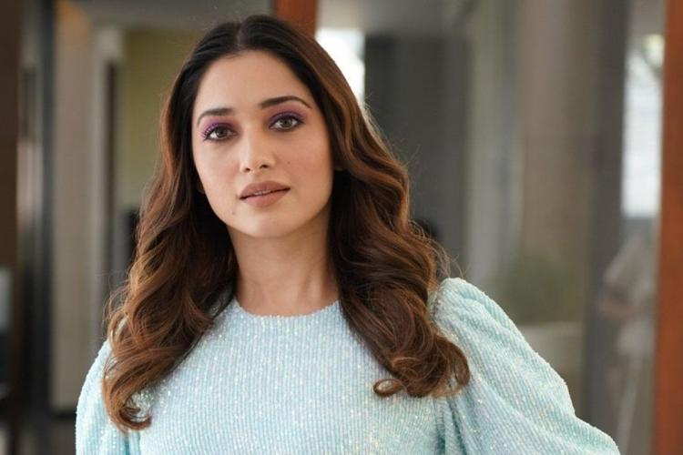 Tammannah wearing a light coloured top with loose hair posing for a picture