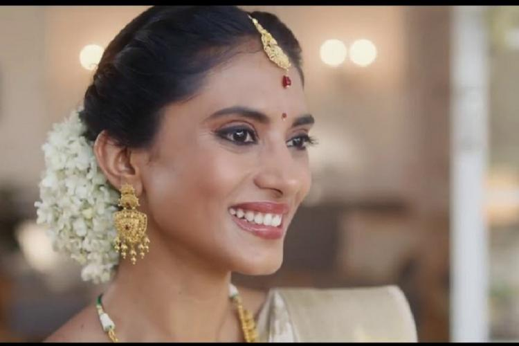A screenshot from the ad shows a woman in a saree adorned with jewellery smiling and looking away from the camera