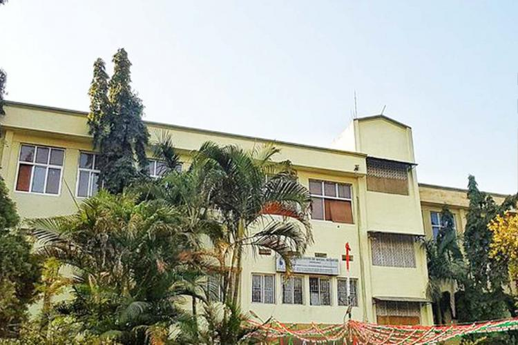 A pale green building in the TISS Hyderabad campus with trees in the foreground